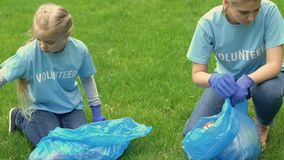 Mother and little girl volunteers collecting trash in park, giving high-five. Stock footage stock video footage