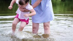 Mother of the little girl washes his feet in the river. Woman playing with her baby on the beach stock footage