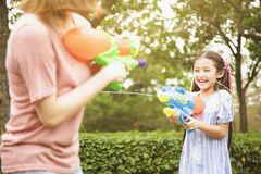 Mother and little girls playing water guns in the park royalty free stock images
