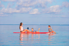 Mother and little girls on surfboard during summer Royalty Free Stock Photo
