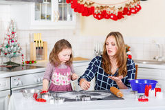 Mother and little kid girl baking gingerbread cookies for Christ Stock Photo