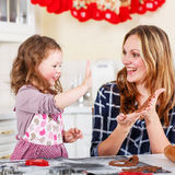 Mother and little kid girl baking gingerbread cookies for Christ Stock Photography