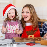 Mother and little kid girl baking gingerbread cookies for Christ Royalty Free Stock Images