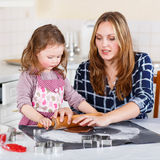 Mother and little kid girl baking gingerbread cookies for Christ Stock Images