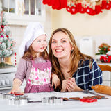 Mother and little kid girl baking gingerbread cookies for Christ Royalty Free Stock Image