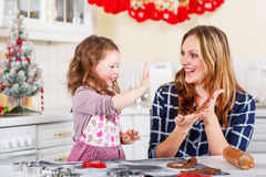 Mother and little kid girl baking gingerbread cookies for Christmas Royalty Free Stock Image