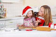 Mother and little kid girl baking gingerbread cookies for Christmas Stock Image