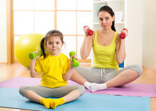 Mother and little kid spending time in gymnastics at home room Stock Photo