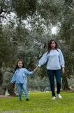 Mother and little Peruvian girl walking together in the park stock image