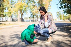 Mother and little son in an autumn park outdoors. Happy boy and young mother painting with chalk Royalty Free Stock Photography