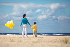 Mother and little son with ballons on the beach Stock Image