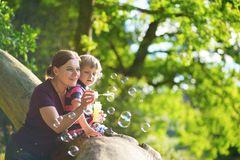 Mother with little son blowing bubbles Royalty Free Stock Image