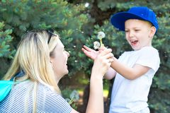 Mother and little son blowing on a dandelion. stock photography
