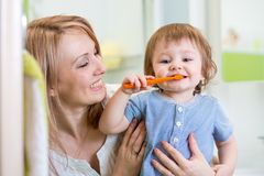Mother and little son brushing teeth in bathroom. Smiling mother and kid son brushing teeth in bathroom royalty free stock image