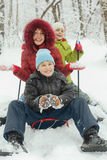 Mother, little son and daughter ride on sled Stock Photos