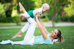 Mother and little son doing exercise outdoors. Healthy lifestyle. Yoga Stock Photo