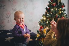 Mother and little son at home near Christmas tree Stock Photography