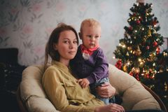 Mother and little son at home near Christmas tree Royalty Free Stock Photo