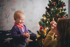 Mother and little son at home near Christmas tree Royalty Free Stock Images