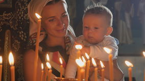 Mother and little son observes the burning candles in the church stock footage