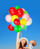 Mother with little son outdoors. Portrait of a happy mother holding her cute little son in one hand and many colorful balloons in another hand over blue sky Royalty Free Stock Photography