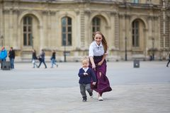 Mother and little son in Paris. Beautiful young mother and her adorable toddler son having fun together in Palais Royal in Paris, boy is running from his mommy Royalty Free Stock Photo