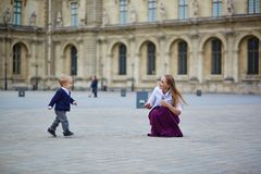 Mother and little son in Paris. Beautiful young mother and her adorable toddler son having fun together in Palais Royal in Paris, boy is running to his mommy Royalty Free Stock Image