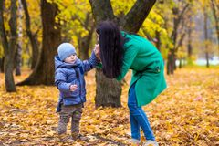 Mother with little son in park on background of autumn leaves Royalty Free Stock Image