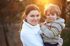 Mother and little son in park or forest, outdoors. Hugging and having fun together. Happy toddler boy and young mum, kid and women playing Royalty Free Stock Photography
