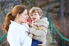 Mother and little son in park or forest, outdoors. Hugging and having fun together. Happy toddler boy and young mum, kid and women playing Royalty Free Stock Image