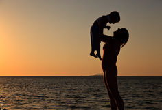 Mother and little son play at sunset sky Royalty Free Stock Photography