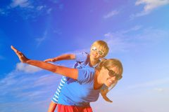 Mother and little son playing airplane on summer Stock Image