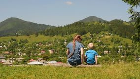 Mother and little son are playing on a green meadow against the background of the village and mountains.  stock video