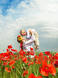 Mother with little son on the poppies  field. Happy ukrainian mother with his little son among the blossom poppies Stock Image