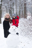 Mother, little son and snowman. Stock Photo