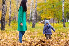 Mother with little son in park on background of autumn leaves Royalty Free Stock Photos
