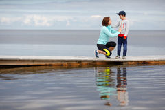 Mother and little son together on wooden jetty Royalty Free Stock Images