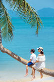 Mother and little son at tropical beach sitting on palm tree Royalty Free Stock Photos