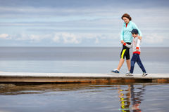 Mother and little son walking together on wooden stock photos