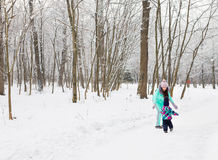 Mother and little toddler girl walking in the winter forest and having fun with snow. Family enjoying winter. Christmas Stock Images