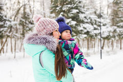 Mother and little toddler girl walking in the winter forest and having fun with snow. Family enjoying winter. Christmas Stock Photos