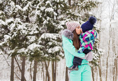 Mother and little toddler girl walking in the winter forest and having fun with snow. Family enjoying winter. Christmas Stock Photography