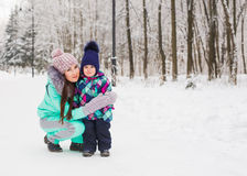 Mother and little toddler girl walking in the winter forest and having fun with snow. Family enjoying winter. Christmas Royalty Free Stock Image