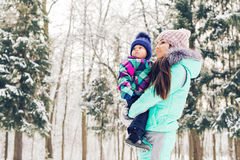 Mother and little toddler girl walking in the winter forest and having fun with snow. Family enjoying winter. Christmas Stock Photo
