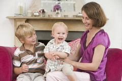 Mother in living room with baby and young boy Stock Photos
