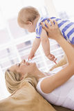 Mother in living room holding baby royalty free stock image