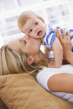 Mother in living room kissing baby Royalty Free Stock Photo