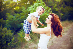 Mother with long curly red hair playing with her son in the park Royalty Free Stock Photos
