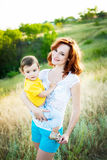 Mother with long curly red hair playing with her son in the park Royalty Free Stock Photography