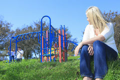 Mother look at boyfriend and children play on the. A mother look at boyfriend and children play on the playground Royalty Free Stock Photos